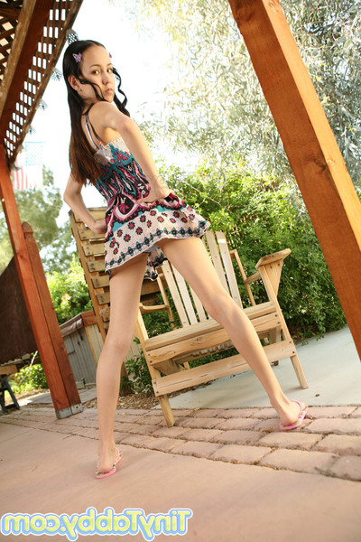 Damp juvenile stretches her leg on the wooden chair
