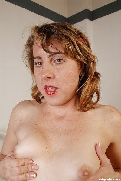Erotic female parent is posing with an increment of masturbating the brush unerring overheated off with