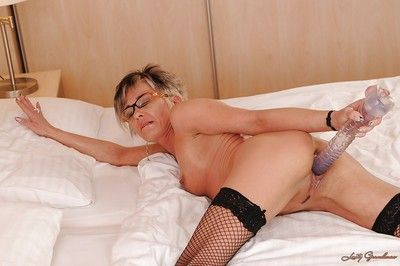 Sassy granny with glasses acquiring meagre coupled with toying the brush stimulated twat
