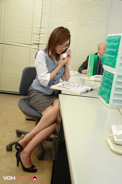 Executive Pair Does A Secretary At Her Desk In The Office.