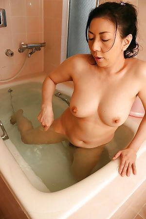 Sassy Chinese MILF Kumiko Yasue teasing her furry muff right after bathroom