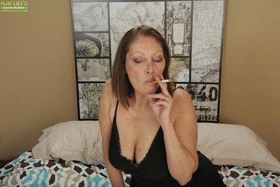 Chunky breasted matured woman Jane McWilliams smoking a cigarette