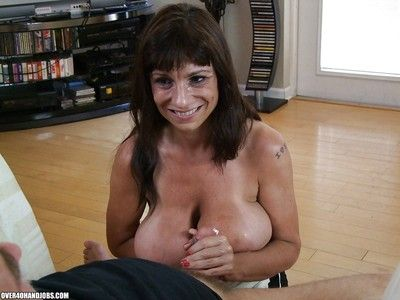 Fuckable grown-up brunette with Herculean knockers gives a sensual handjob