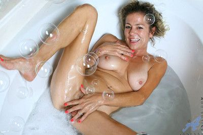 Experienced cougar vanessa enjoys the brush seethe bath with regard to a black vibrator banging