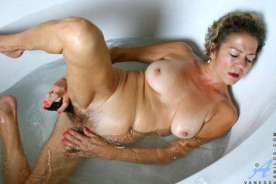 Experienced cougar vanessa enjoys the brush seethe bath with regard to a black vibrator banging