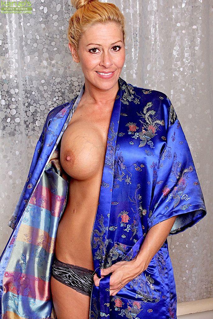 Buxom mature blonde Kaycee James masturbating shaved pussy close to bath