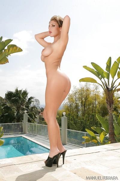 Busty blond MILF pornstar Velicity Von poses beside swimming pool in bikini
