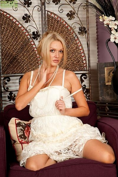 Sexy blonde mummy in white dress striking alluring poses in stockings