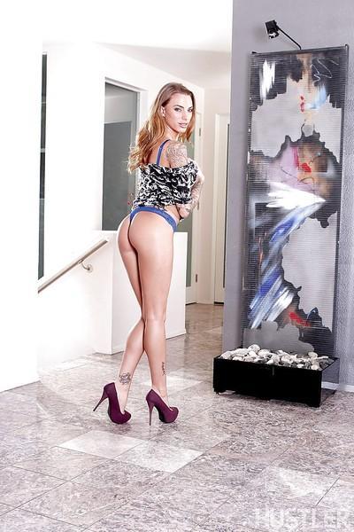 Tattooed MILF Juelz Ventura posing solo in thong panties and high heels