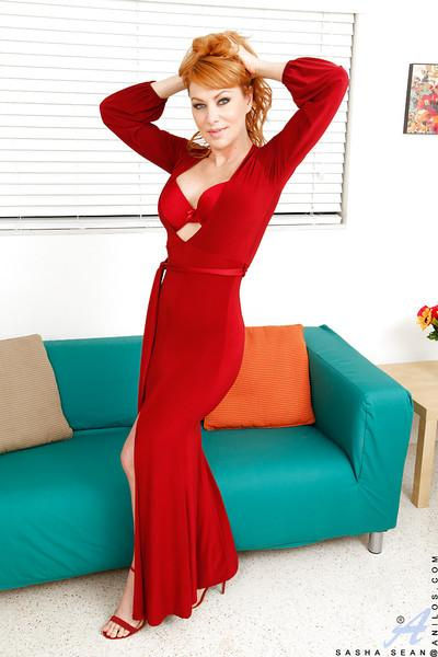 Redheaded MILF Sasha Sean poses fully clothed in bright red dress