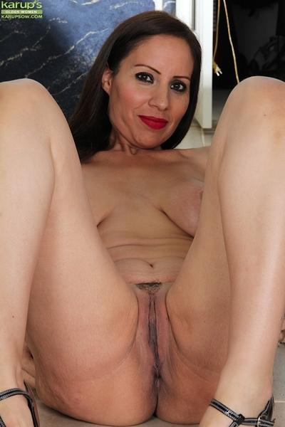 Brunette milf babe Carmen Jones is showing her pussy while spreading legs