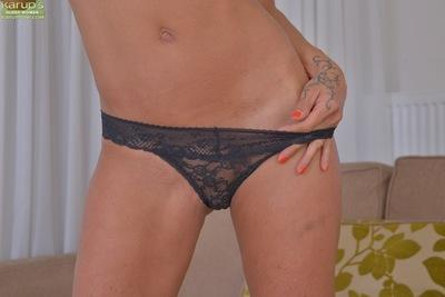 Leggy blonde babe strips off lingerie and panties to expose shaved pussy