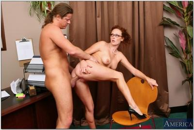 Redhead MILF in glasses Audrey Hollander takes deep anal in the office
