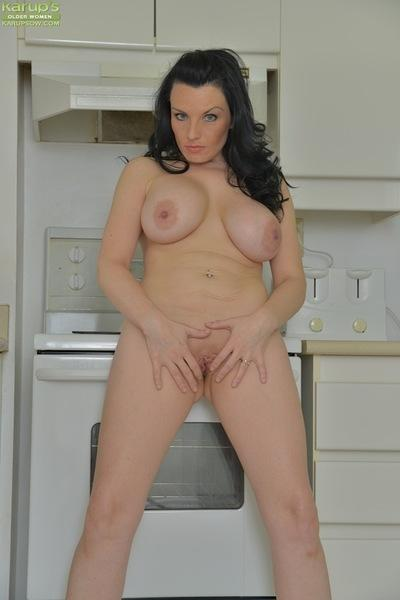 Brunette MILF Stacy Ray slipping panties and skirt over ass in kitchen
