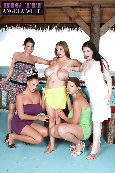 Busty MILF lesbians oil up big knockers outdoors in beach setting