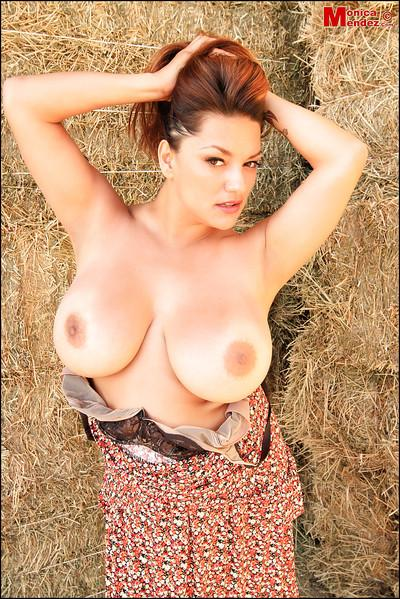 Redhead big-tit pornstar Monica Mendez poses in the hayloft