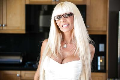 Well-toned mature blonde in glasses slowly uncovering her fuckable body