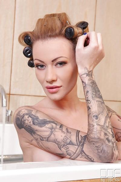 Tattooed sex slut Becky Holy posing her big natural tits in bath