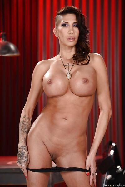 Busty MILF model Kayla Carrera strips naked except for leather boots