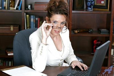 Gorgeous secretary MILF in glasses denudes her melons and snatch in the office