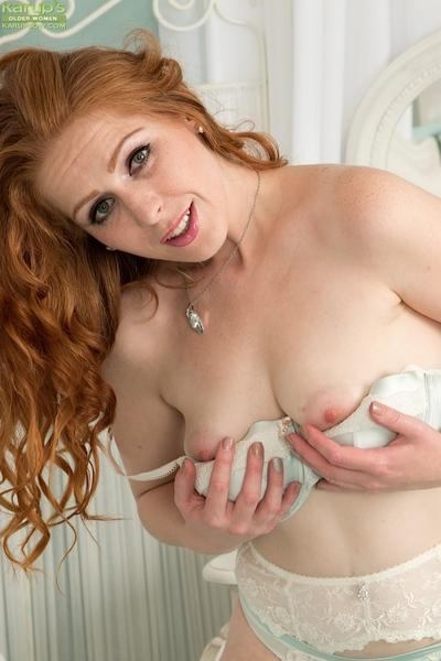 Stocking clad redhead babe Tia Jones exposing hairy MILF vagina and ass