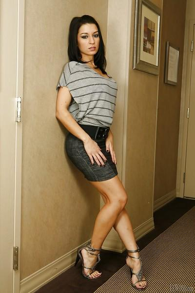Brunette pornstar Ann Marie Rios demonstrates her long legs in a skirt