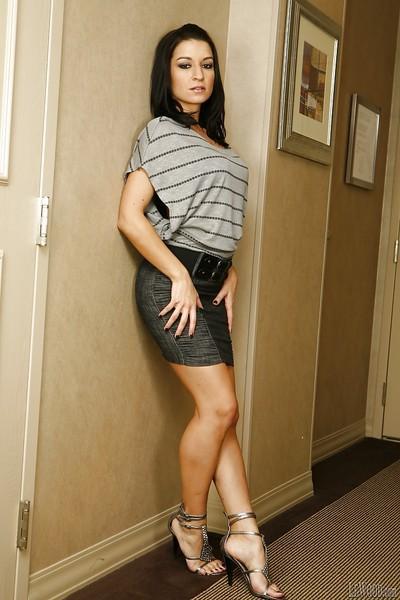 Brunette pornstar Ann Marie Rios demonstrates her long legs in a skirt