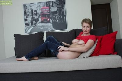 Fit MILF Sweet Nensy modeling topless in blue jeans on couch