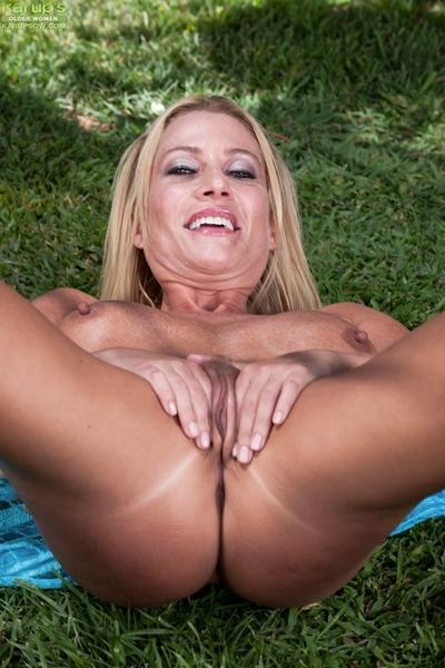 Naughty blonde MILF showing off her sexy soles and teasing her gash outdoor