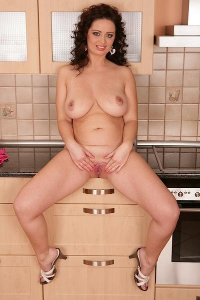 Buxom babe Sirale letting her large natural knockers loose in the kitchen