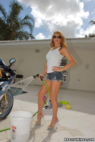 Milf in revealing bikini washes bike with her big tits bare
