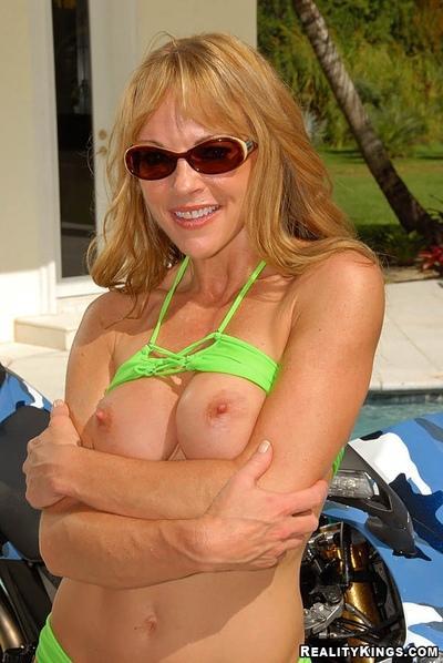 Milf in revealing bikini washes bike with her big tits bare
