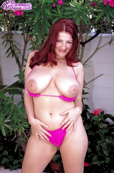 Redheaded MILF model Lorna Morgan releasing nice melons from bikini outside