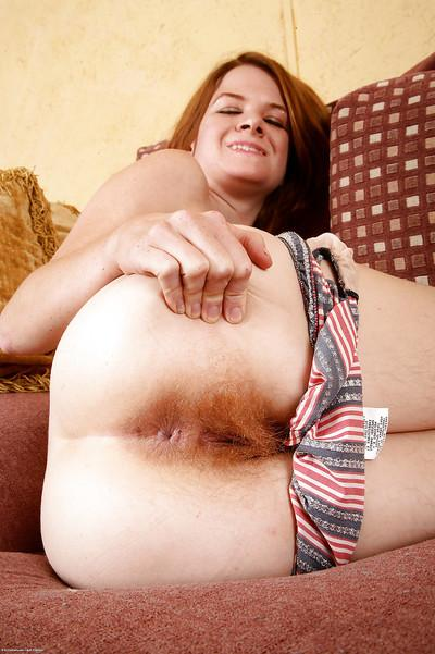 Sassy redhead undressing and exposing her hairy armpits and shaggy twat