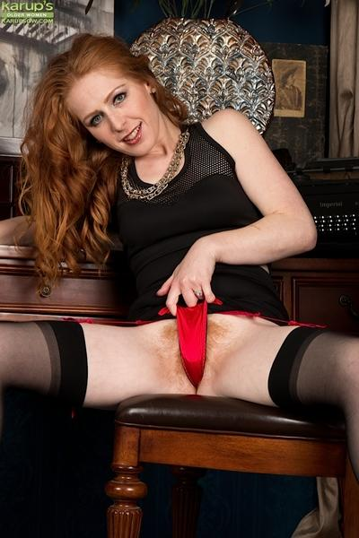 Stocking attired redhead babe Tia Jones spreading hairy MILF pussy