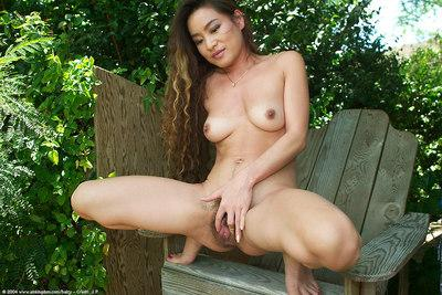 Horny brunette Asian amateur Leilani spreading her hairy pussy and pissing