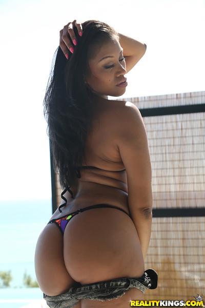 Ebony babe Yasmine De Leon posing in sunglasses and bikini on beach
