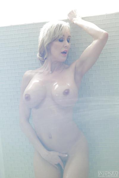 Buxom blonde pornstar Brandi Love pressing big wet tits up against glass