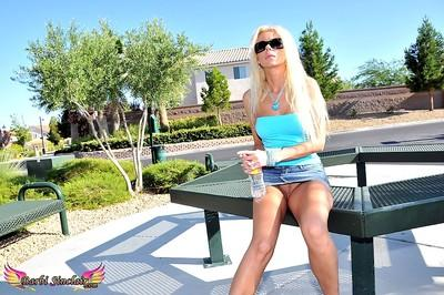 Barbi Sinclair wears glasses as she poses outdoors in high heels and mini skirt.