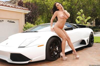 Wooing brunette temptress on high heels stripping off her bikini outdoor