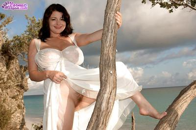 Brunette Euro mom Lorna Morgan frees large boobs and upskirt pussy on beach