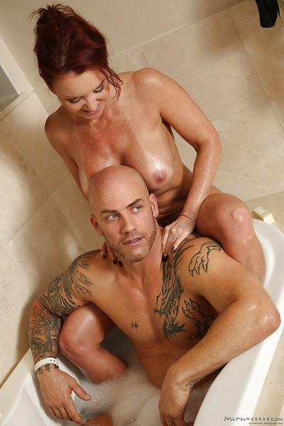 Naked cougar Janet Mason giving younger man a massage in bathtub