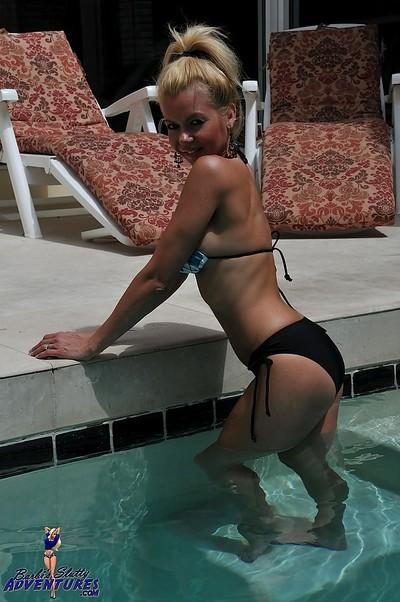 Cute blonde MILF Barbi Sinclair shows her fantastic body wearing sexy bikini in the pool.