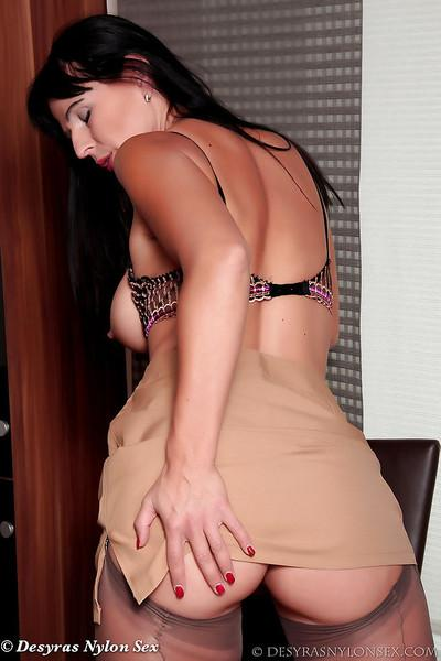 Brunette chick Desyra Noir spreading nylon clad legs to expose cooter