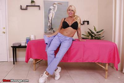 Older blonde nurse stripping off uniform to pose naked on massage table