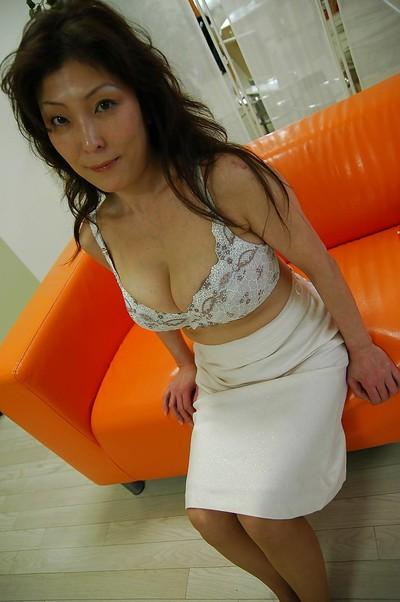 Busty asian MILF Masako Suzuki getting naked and spreading her lower lips