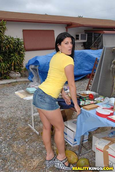 Dark-haired milf with big tits and ass barely covered by skirt