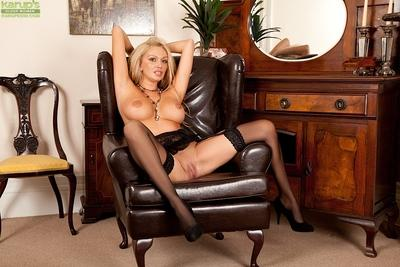 Blonde MILF Amber Rayne posing topless in stockings and garters