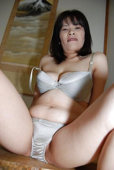 Asian milf Yumiko undressing her big boobs and hairy pussy