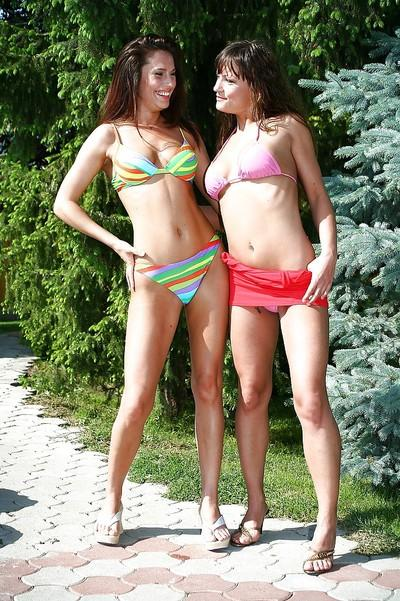 Seductive brunette ladies in bikinis have a lesbian sex outdoor